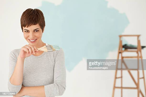 Junge Frau lächelnd Holding Paint Brush