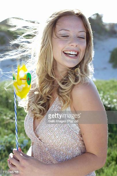 Young woman smiling holding pin wheel, Cape town, South Africa