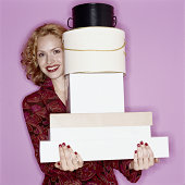 Young woman smiling holding tall stack of boxes, portrait