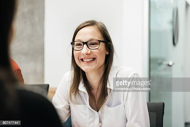 Young woman smiling in a business meeting.