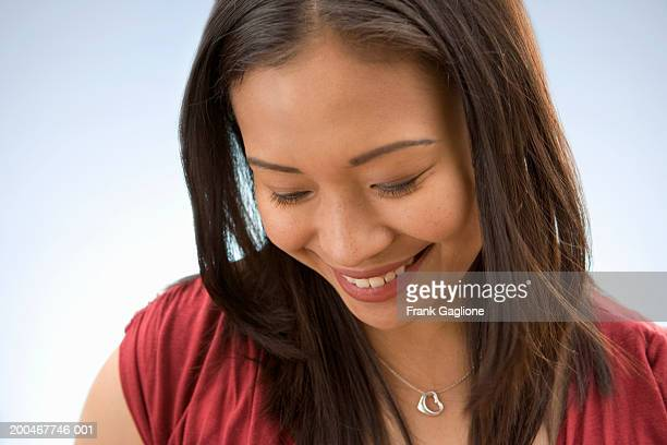 Young woman smiling, looking down