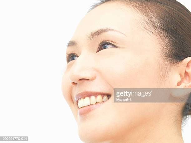 Young woman smiling, looking up