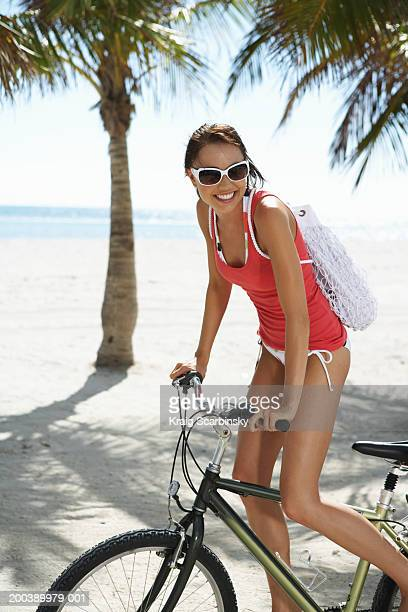 Young woman smiling on bicycle, close-up