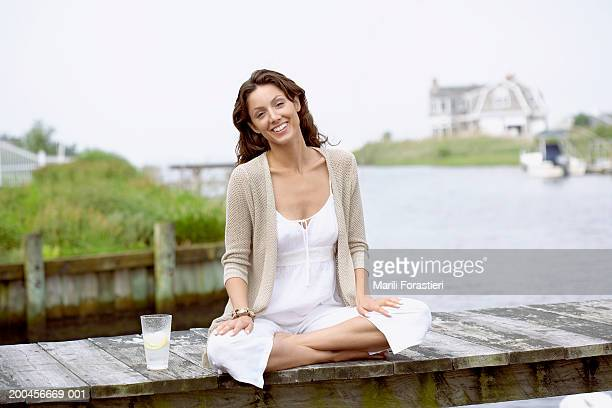 Young woman smiling on dock with beverage, portrait