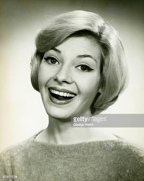 Young woman smiling, posing in studio, (B&W), (Portrait)