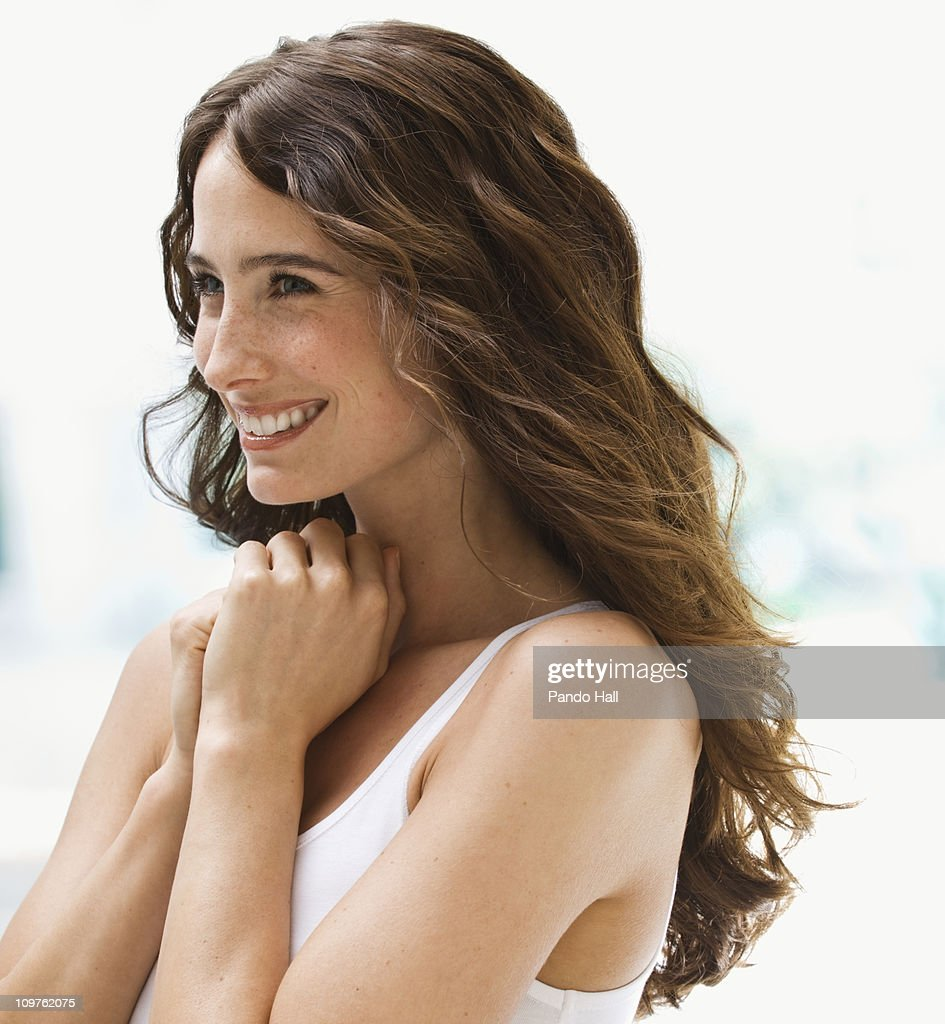 Young woman smiling, side view, close-up : Stock Photo