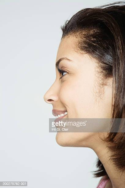 Young woman smiling, side view