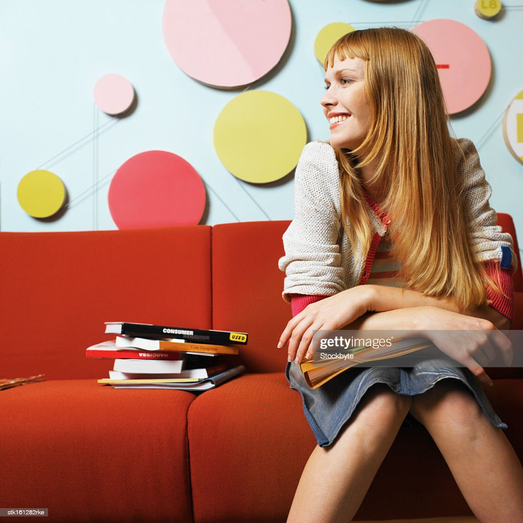 Young woman smiling sitting on a red sofa : Stock Photo