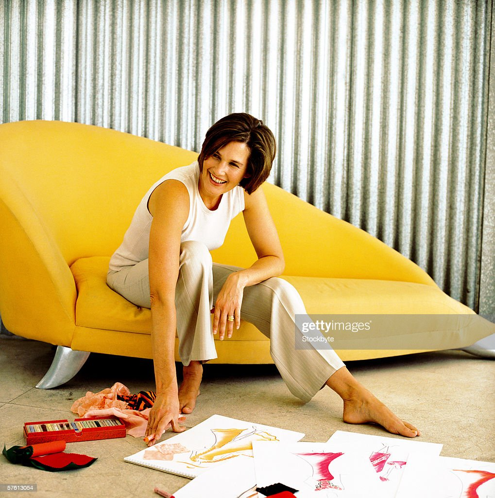 Young woman smiling sitting on a sofa : Stock Photo