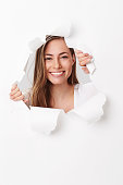 Young woman smiling through tears in paper, portrait