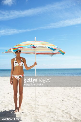 Young woman smiling under beach umbrella, portrait