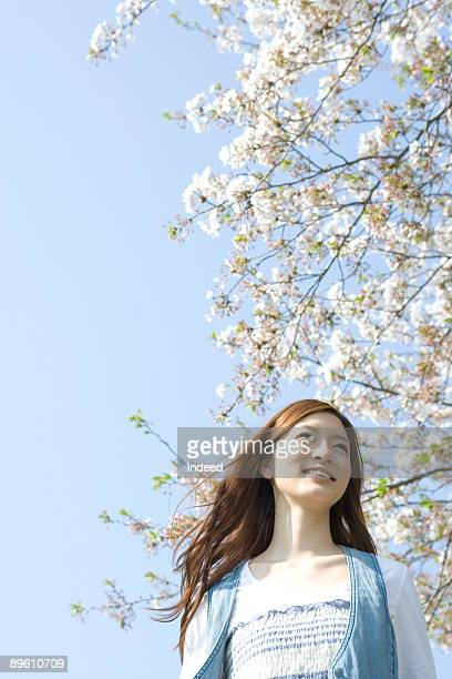 Young woman smiling under cherry tree