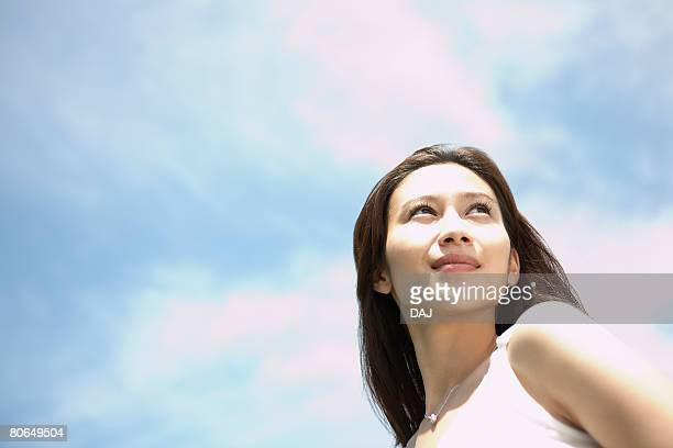 Young woman smiling under the sky, looking back