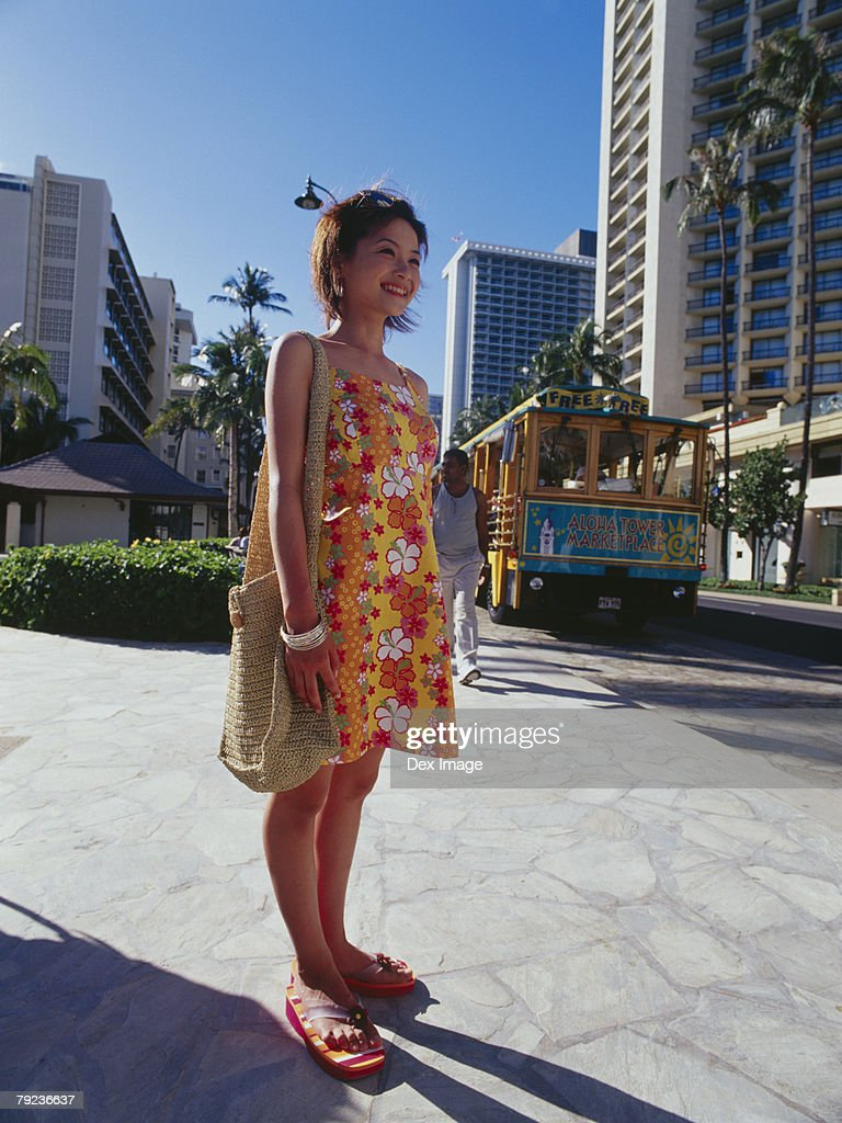 Young woman smiling, urban scene in background : Stock Photo