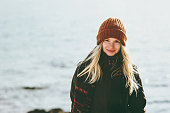 Young Woman smiling walking at winter sea Travel Fashion Lifestyle concept outdoor. Girl wearing orange hat and scarf cold weather
