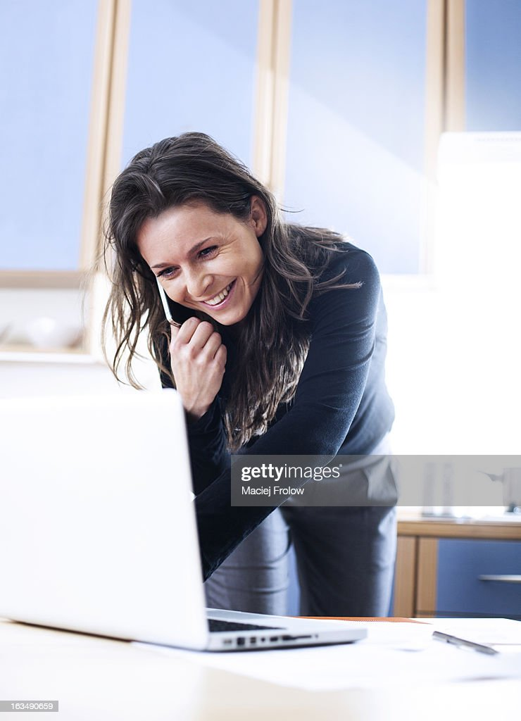 Young woman smiling when talking on a phone : Stock Photo