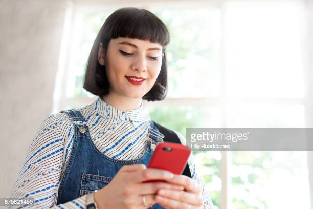 Young woman smiling while texting
