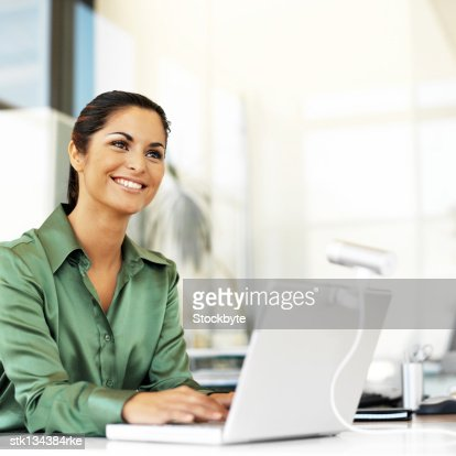 young woman smiling while using a laptop : Stock Photo