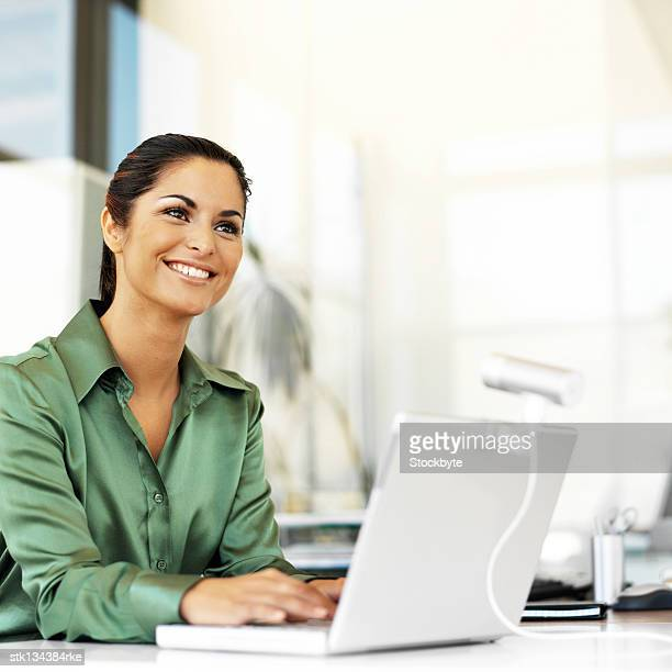 young woman smiling while using a laptop