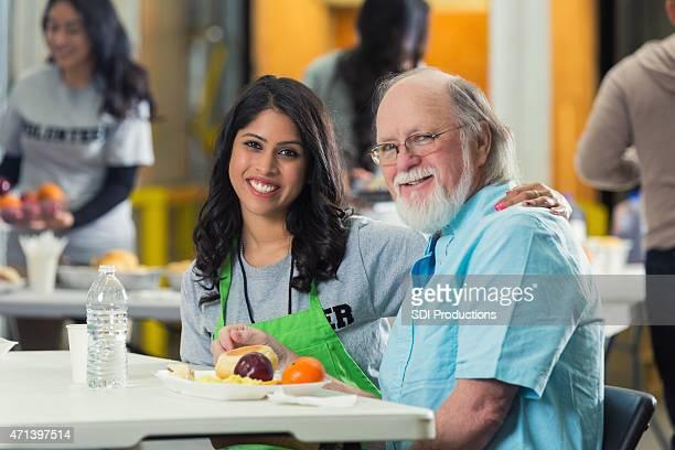 Jeune femme souriant tandis que de bénévolat auprès des séniors à la banque alimentaire