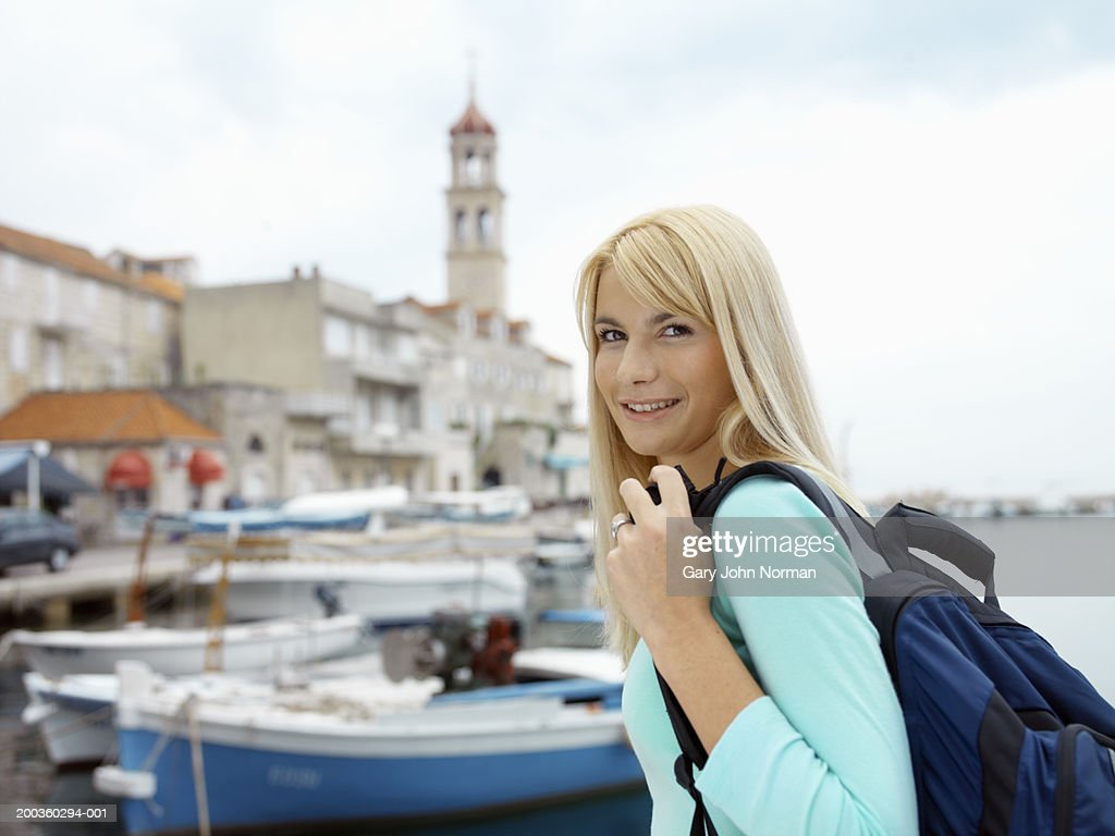 Young woman smiling with backpack near harbor, portrait : Stock Photo