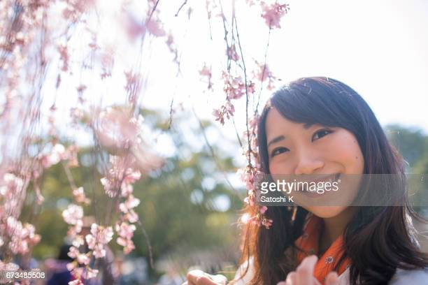 Young woman smiling with cherry blossoms