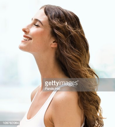 Young woman smiling with eyes closed, side view