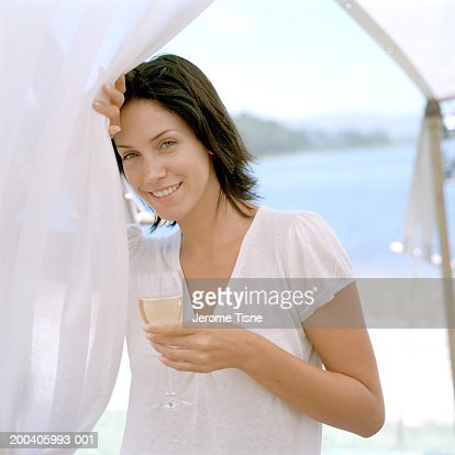 Young woman smiling with glass of wine under tent, portrait, close-up