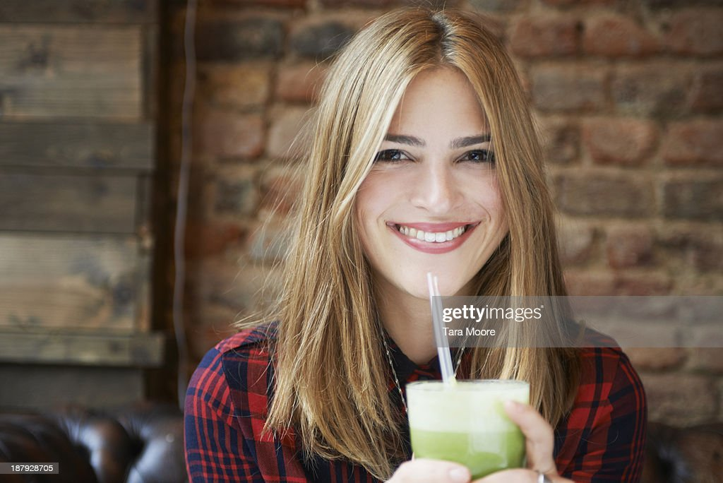 young woman smiling with healthy juice