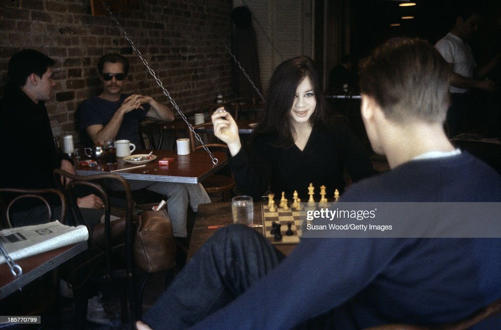 A young woman smokes a cigarette as she plays chess against a young man in a coffeeshop in the Greenwich Village neighborhood, New York, New York, March 1962.