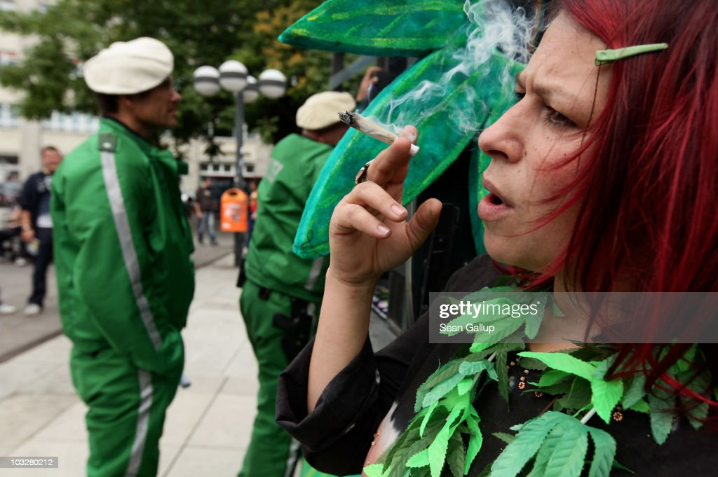 A young woman smokes a legal herb called damian as policemen stand nearby prior to marching in support of the legalization of marijuana in Germany during the annual Hemp Parade, or 'Hanfparade', on August 7, 2010 in Berlin, Germany. The consumption of cannabis in Germany is legal, though all other aspects, including growing, importing or selling it, are not. However, since the introduction of a new law in 2009, the sale and possession of marijuana for licenced medicinal use is legal.