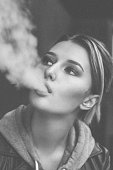 Portrait of a Young Woman smoking electronic cigarette. Black and white post processing
