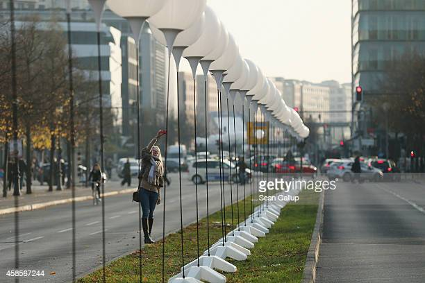 A young woman snaps a photo of lamps tethered to balloons that are part of a light installation to commemorate the 25th anniversary of the fall of...