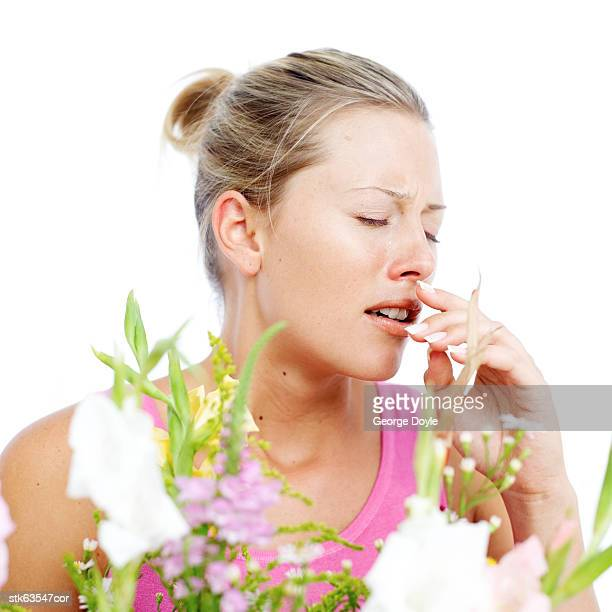 young woman sneezing due to pollen dust from flowers
