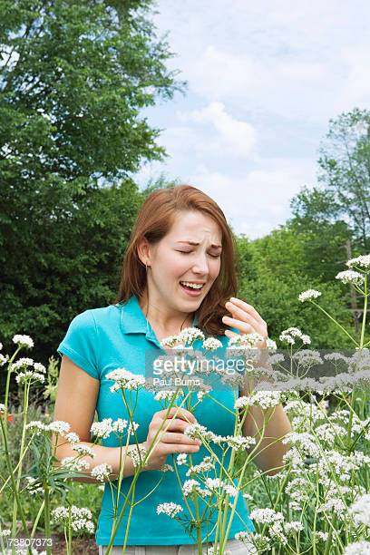 Young woman sneezing near flowers in garden