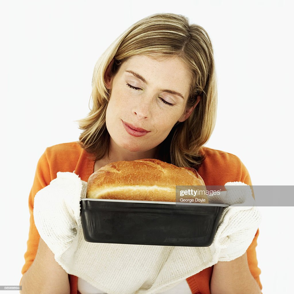 young woman sniffing a loaf of freshly baked bread : Stock Photo