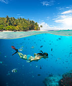 Young woman snorkling on tropical beach. Underwater sports and tropical vacation template