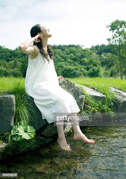 Young woman soaking feet in river