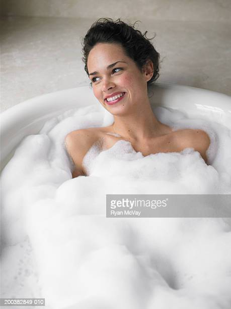 Young woman soaking in bubble bath, smiling, elevated view