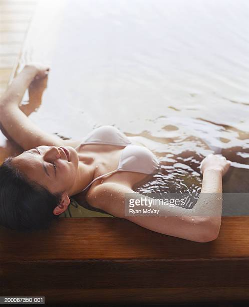 Young woman soaking in hot spring bath, eyes closed, elevated view