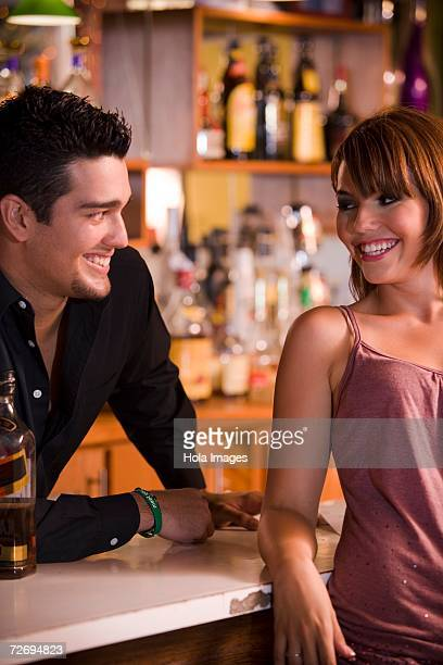 Young woman socializing with bartender at bar, night