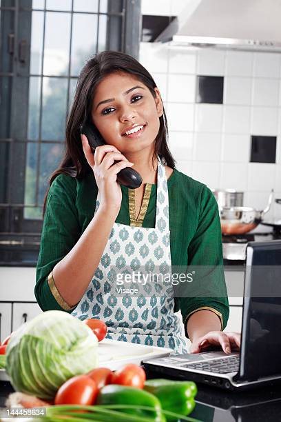 Young woman speaking on phone and working with laptop