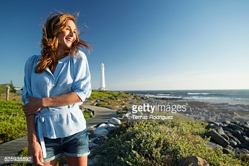 Young woman spending summer day on coastline : Stock Photo