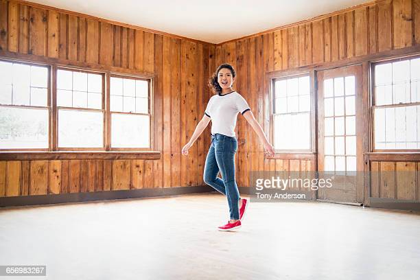 Young woman spinning around in rustic lodge