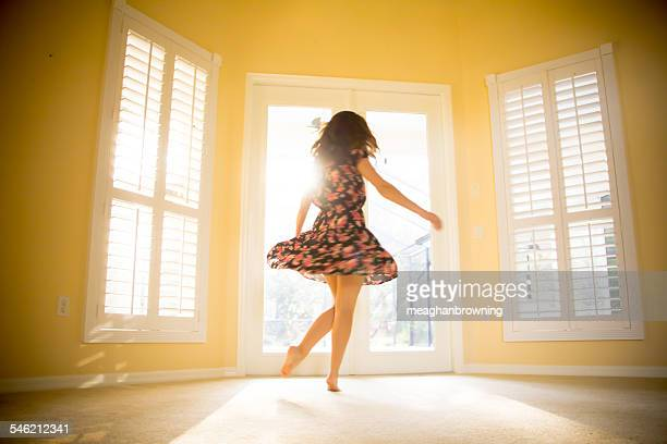 Young woman spinning in sunny room