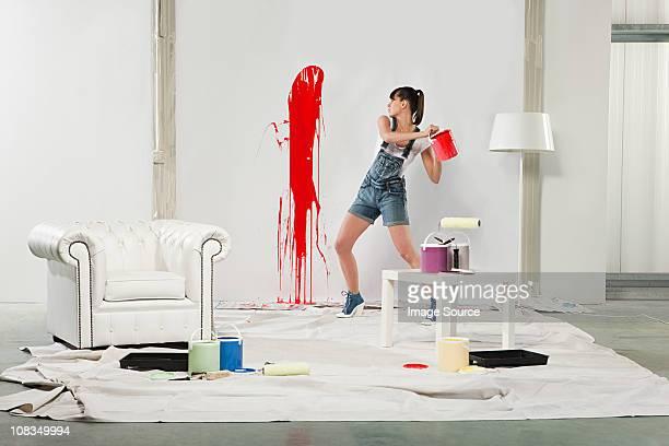 Jeune femme peinture éclaboussures sur blanc Mur rouge