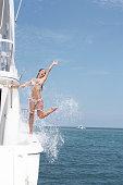 Young woman splashing water aboard yacht
