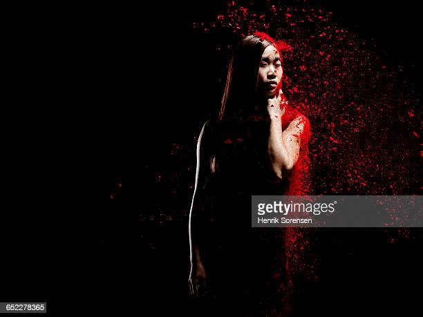 young woman sprayed by red powder