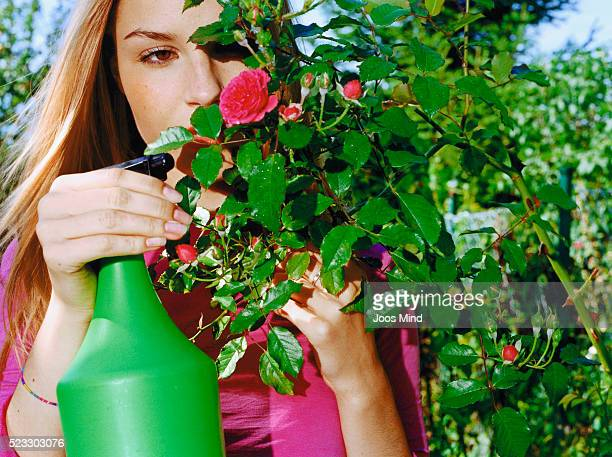 Young Woman Spraying Flowers in Garden