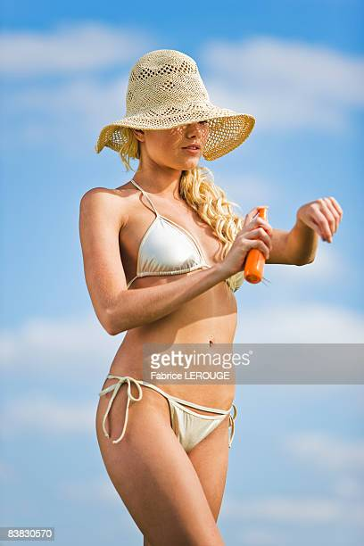 Young woman spraying suncream on her arm